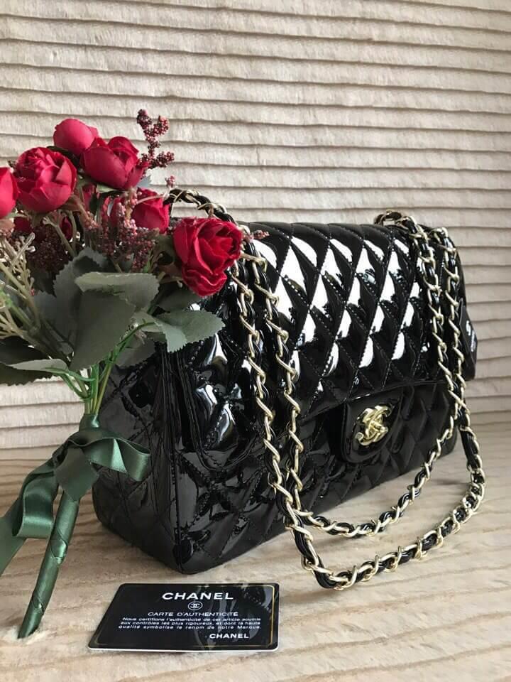 Чёрная сумка выполнена из лаковой кожи